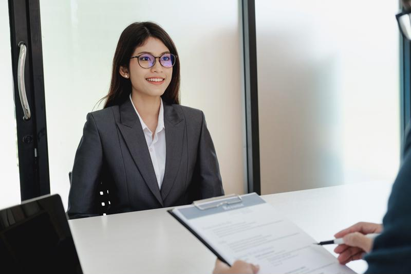 A woman sitting at a table at a job interview.