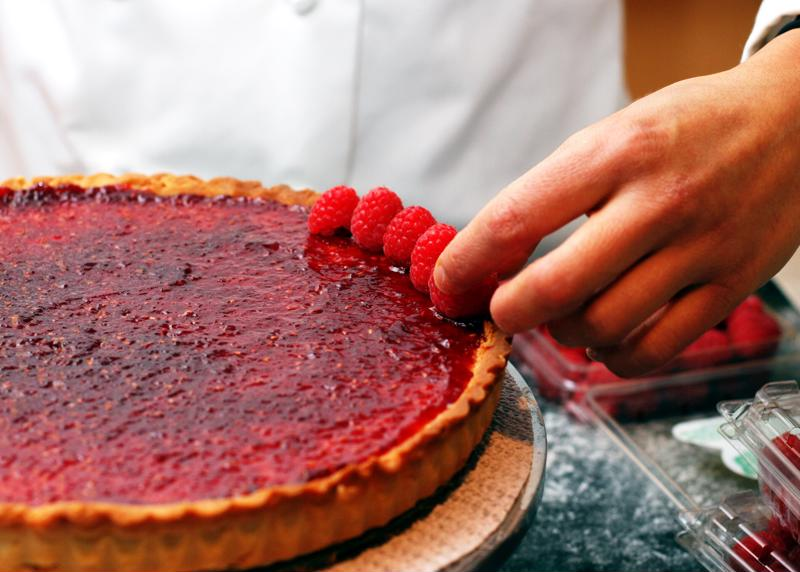 A pastry chef adding raspberries to a dessert.