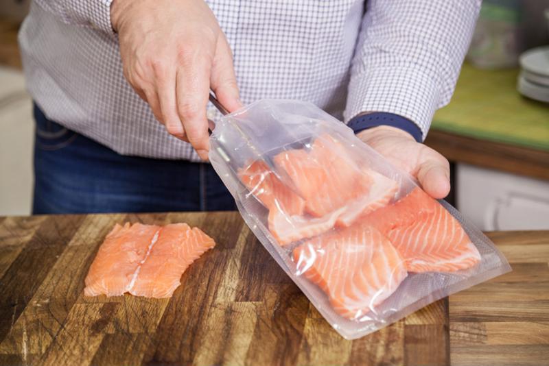 Man placing meat in Foodsaver bag