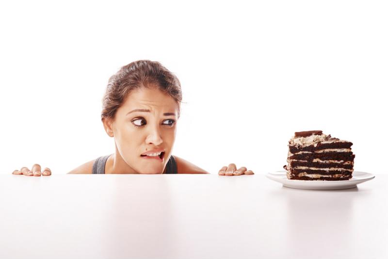 A woman eyeing a slice of cake