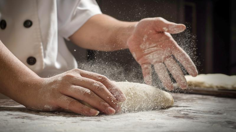 A close-up shot of a chef adding flour to a piece of dough as it's rolled on a table.