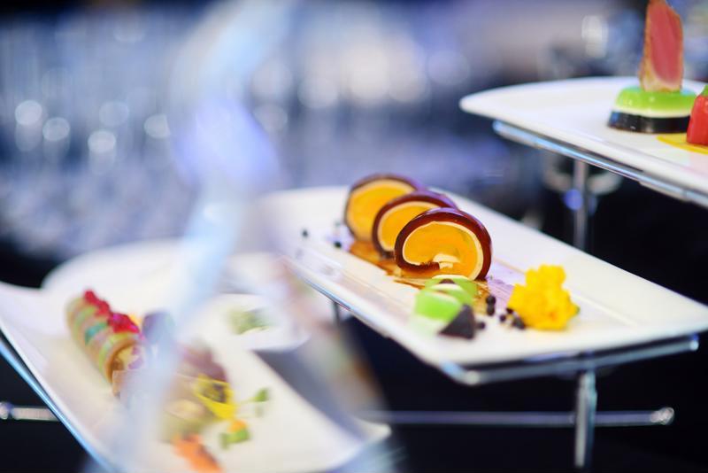A closeup of a few rectangular plates of food.