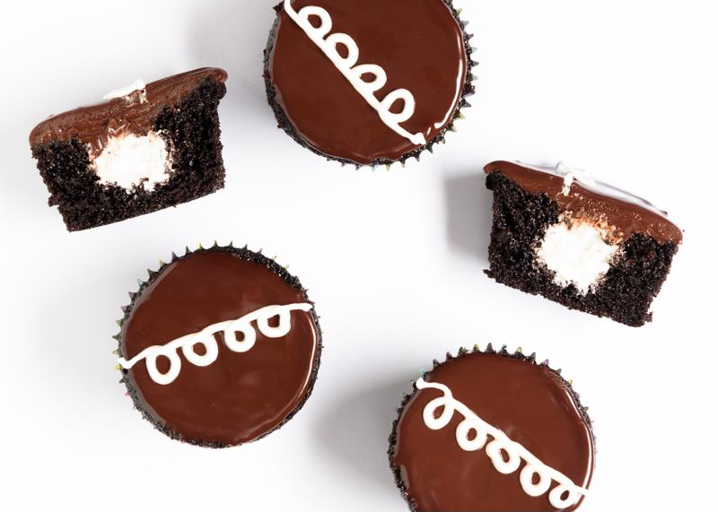 A group of chocolate cupcakes on a neutral background.