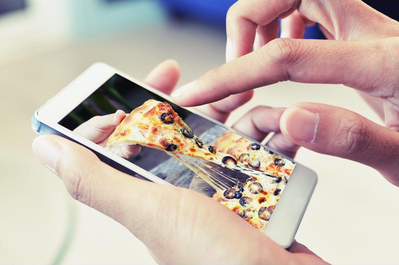 A person looking at a slice of pizza on a smartphone.