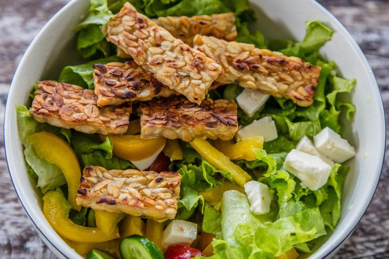 Tempeh over salad is a simple but effective way to prepare a probiotic-rich dish.