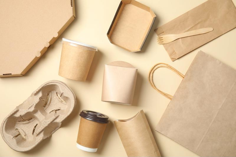 A variety of paper containers lying on a neutral background.
