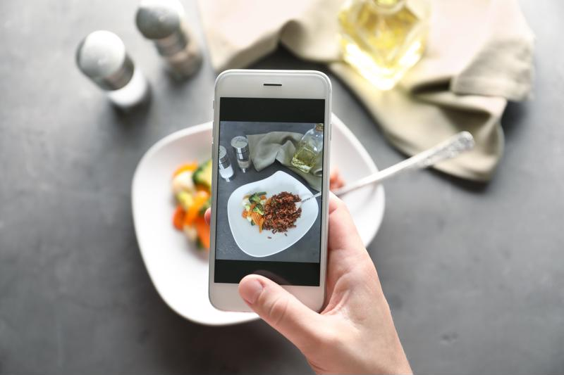 A chef taking a photo of a plated dish on a smartphone.