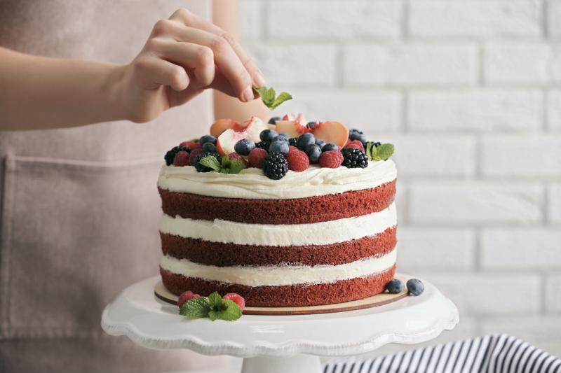 A chef placing a small garnish on a layer cake.