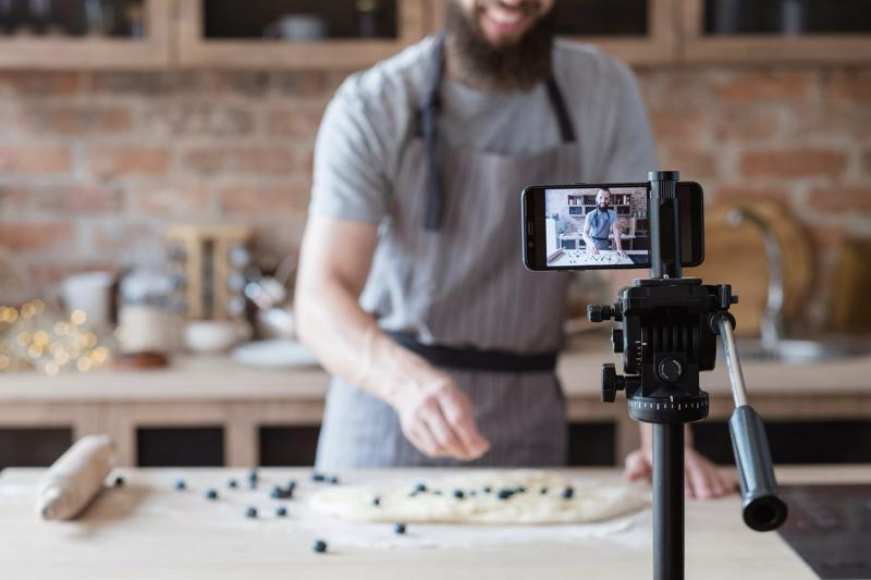 A chef filming himself as he prepares a dish.