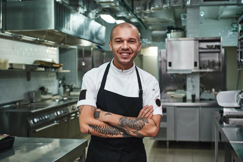 A chef standing in a kitchen, smiling at the camera with arms crossed.