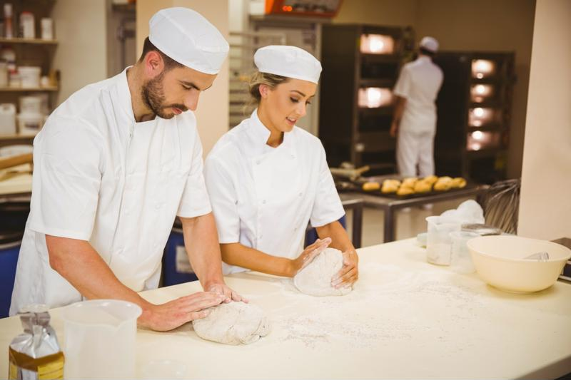 Two chefs prepare dough in a commercial kitchen.