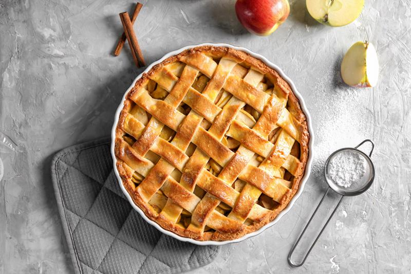 A pie with a lattice crust on a table.