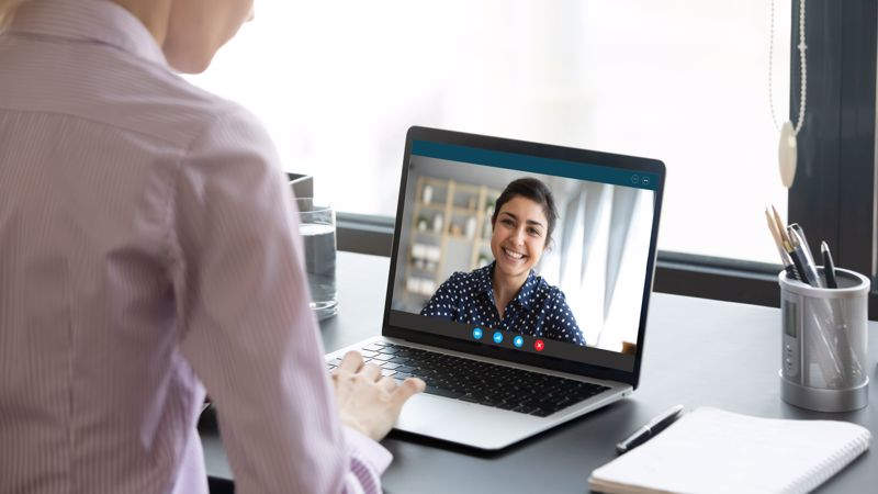 A patient on the computer screen chats with her doctor who is seated in her own office.