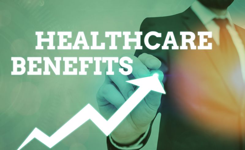 businessman standing behind graphics of the words HEALTHCARE BENEFITS and a rising arrow