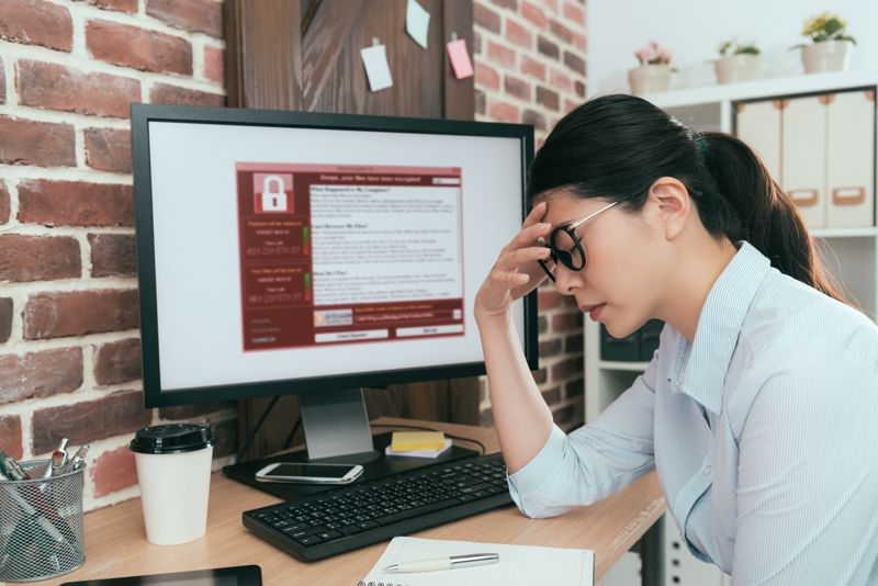 Woman frustrated by computer that's been infected with malware