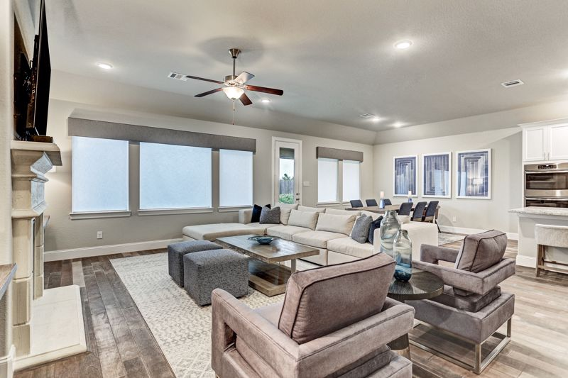 spacious sectional, neutral decor, gray ottomans, coffee table, pair of chairs, fireplace, artwork, open floor plan
