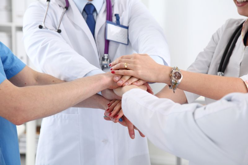 Health professionals touching hands.
