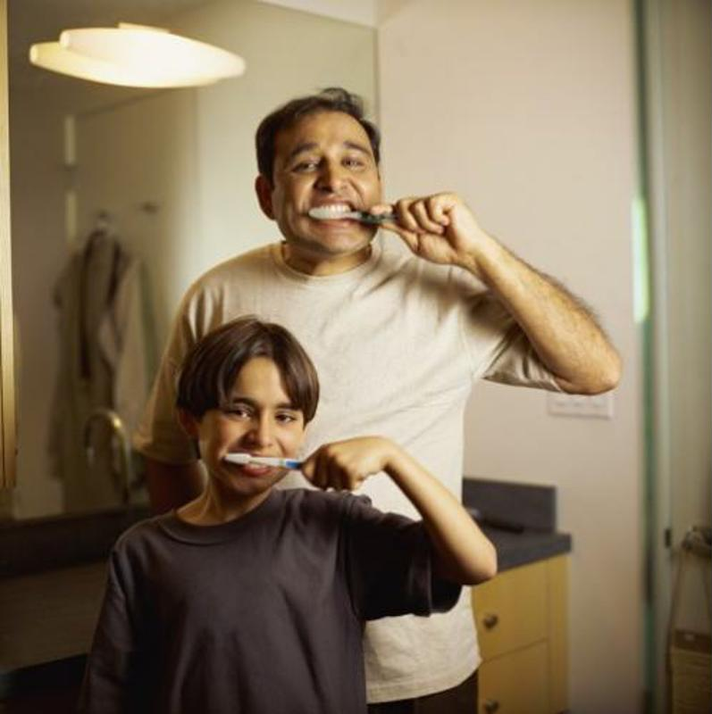 Man and son brushing teeth in front of the mirror.