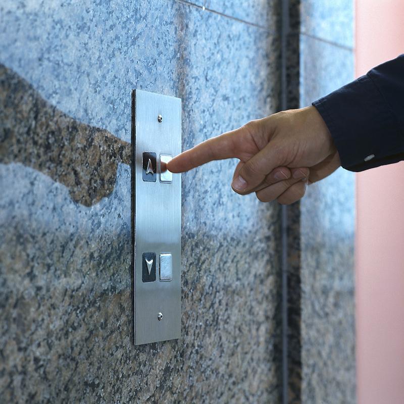 Man pushing elevator button.