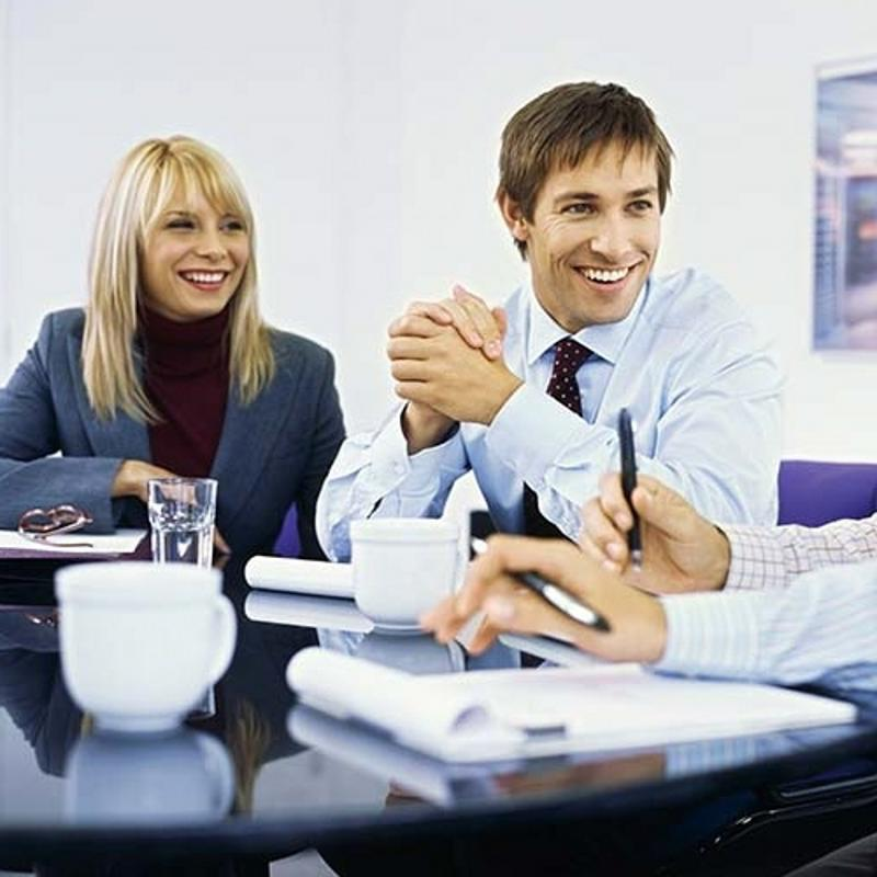 Two co-workers smiling during a meeting.