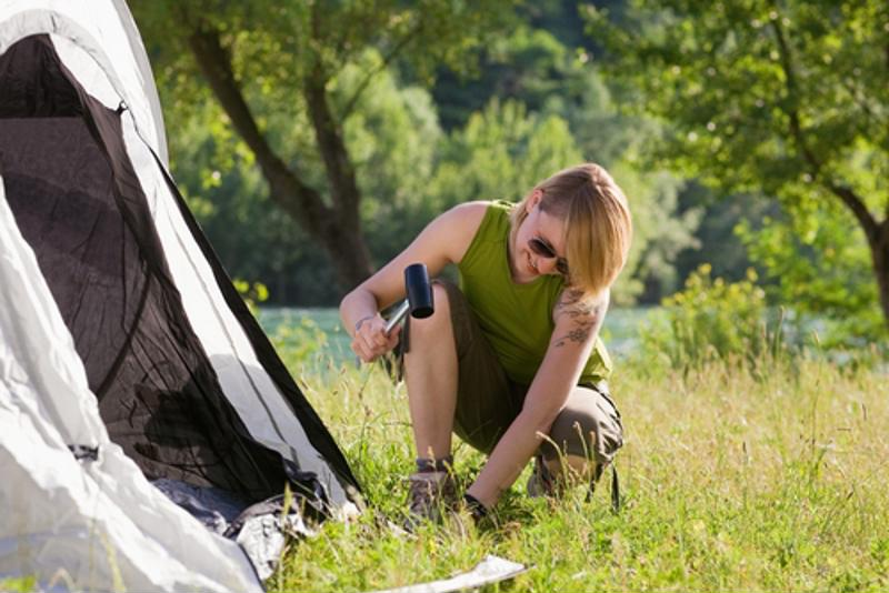 woman pounding in tent stake